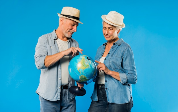 Modern senior couple with globe