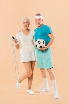 ロープとサッカーをスキップしている現代の高齢カップル