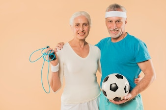Modern senior couple with skipping rope and football