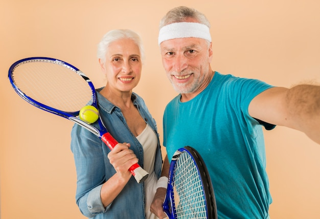 Modern senior couple with tennis racket taking selfie