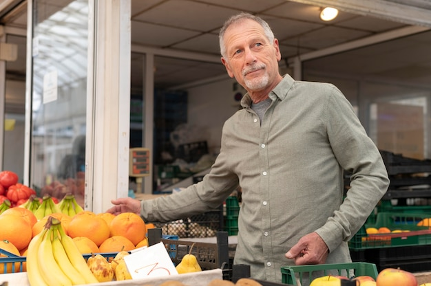 Современный старший мужчина делает покупки продуктов