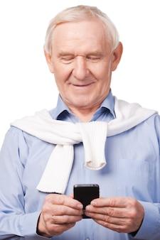 Modern senior man . happy senior man holding mobile phone while standing against white