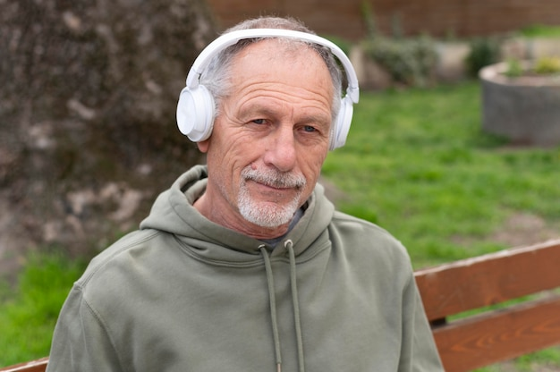 Modern senior man listening to music in a headset