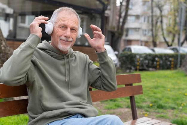 Uomo maggiore moderno che ascolta la musica in una cuffia avricolare