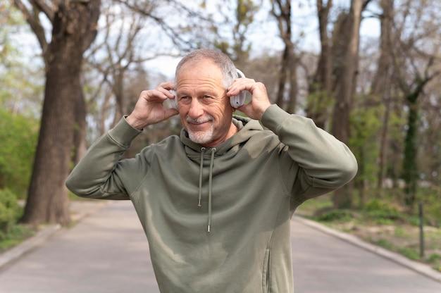 Современный старший мужчина слушает музыку в гарнитуре