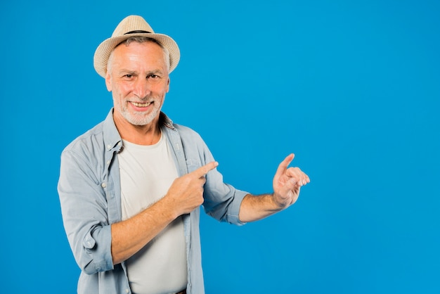 Modern senior man pointing to copyspace