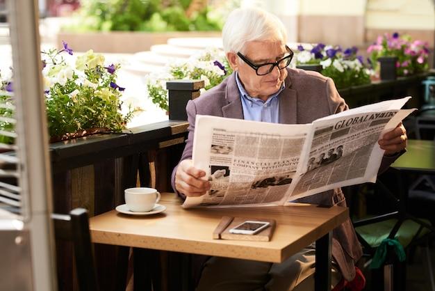 Современный старший мужчина читает газету на открытом воздухе