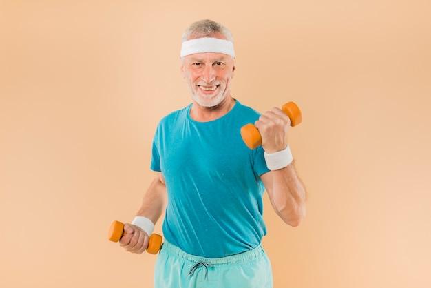 Modern senior man training with dumbbells