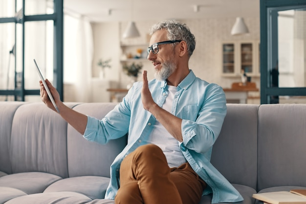 디지털 태블릿을 사용하고 집에서 소파에 앉아있는 동안 손을 흔들며 현대 수석 남자