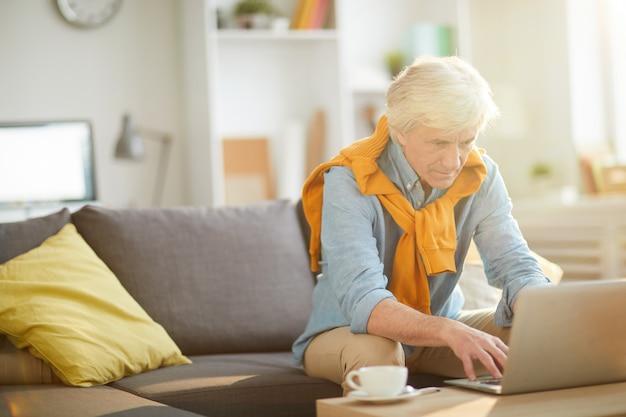 Modern senior man using laptop at home
