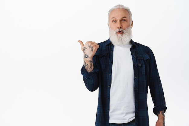 Modern senior man with beard and tattoos pointing left at copy space, showing your logo advertisement, looking surprised at front, standing over white wall