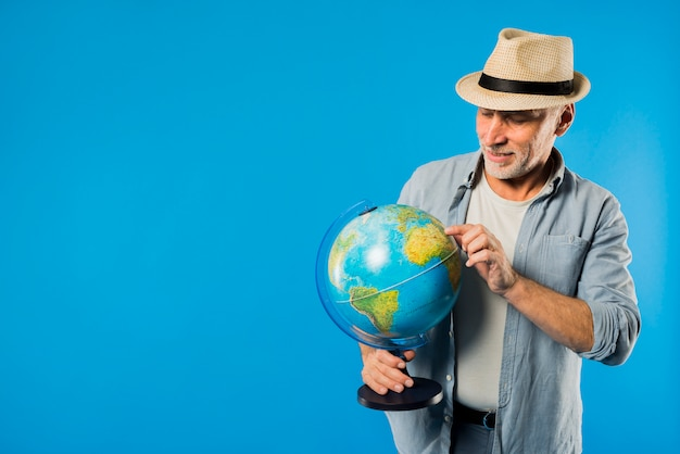 Modern senior man with globe