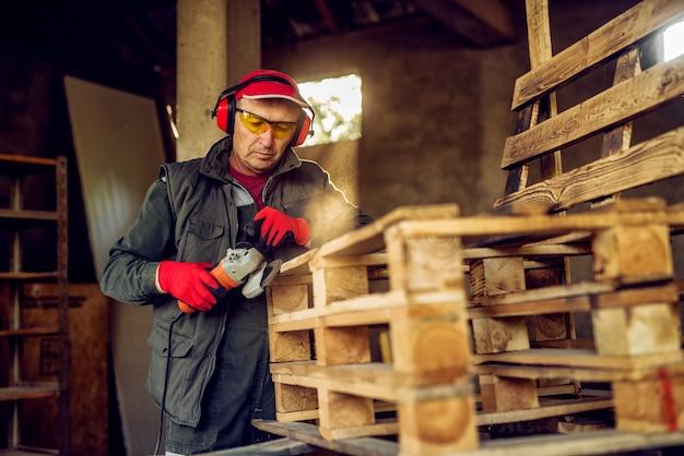ワークショップで電動グラインダーで木製パレットに取り組んでいる保護と制服を着た現代のシニアプロ産業労働者。