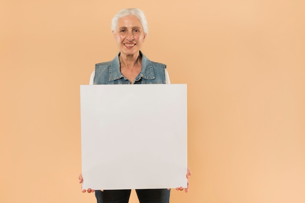 Modern senior woman holding board template