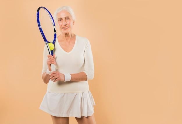 Modern senior woman playing tennis