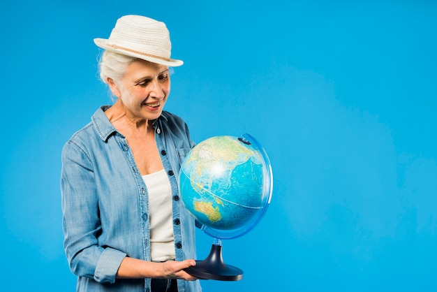 Modern senior woman with globe