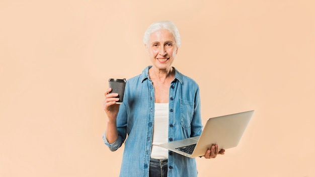 Modern senior woman with laptop and coffee