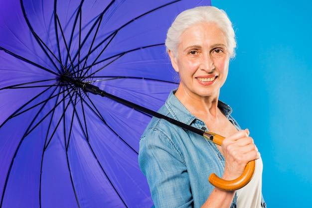 傘を持つ現代のシニアの女性