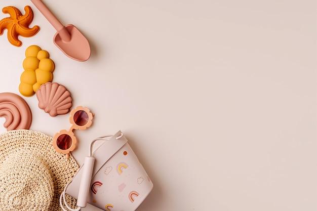 休暇のためのモダンなセット:サングラス、帽子、ビーチおもちゃ。フラットレイ子供のためのビーチサマーアクセサリーの上面図。