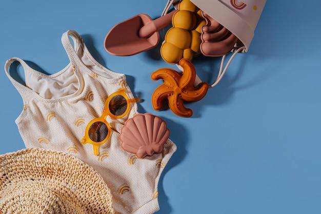 休暇のためのモダンなセット。子供のためのビーチサマーアクセサリーの上面図。ファッション水着、サングラス、帽子、ビーチおもちゃ。フラットレイ