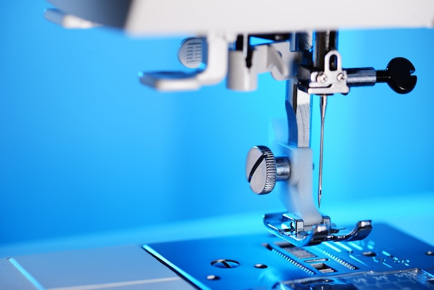 Modern sewing machine foot on blue background