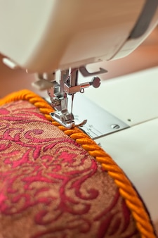 Современная прижимная лапка швейной машины и декоративный окантовочный шнур. процесс шитья.