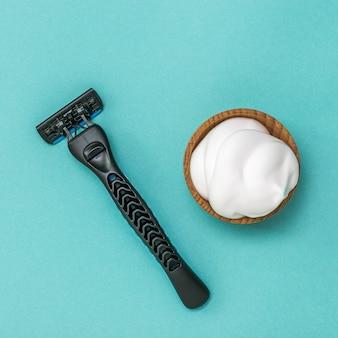 Современный бритвенный станок и пена для бритья в деревянной миске на синем фоне. набор для ухода за мужским лицом. плоская планировка.