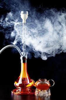 Modern shisha and glass teapot on black background