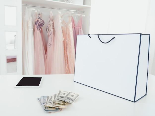 Современный шоппинг. роскошный бутик. дорогая покупка. посылка, куча наличных и планшет в автосалоне.