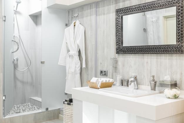 Интерьер современной душевой комнаты с умывальником и зеркалом