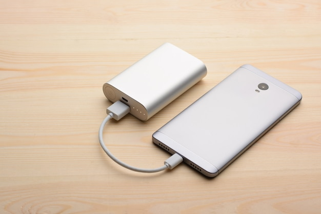Modern silver smartphone lays on light wooden table with its back panel up while charging with power bank