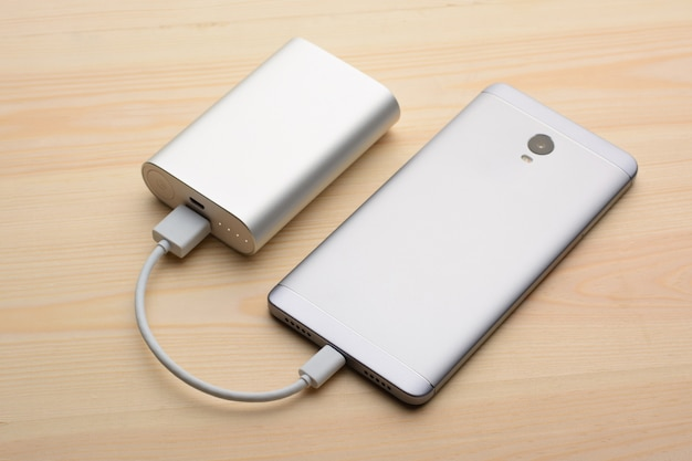 Modern silver smartphone lays on light wooden table with its screen down while charging with power bank