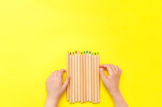 黄色の背景に色のクレヨンでモダンなスケッチセット。カラフルな抽象的な背景。