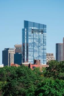 ガラスのファサードと緑が周囲にあるモダンな超高層ビル
