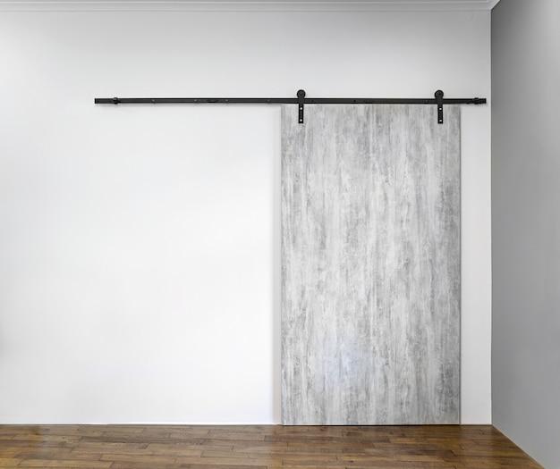 Современная раздвижная серая дверь на белой стене