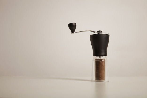 Modern slim manual burr grinder with freshly ground coffee on white table on white wall