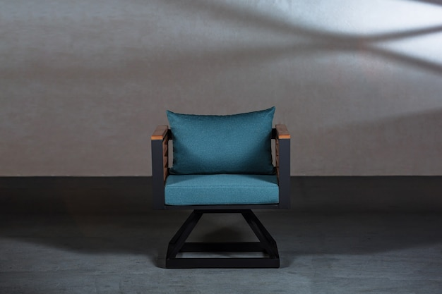 Modern small chair with a blue cushion on it in a room