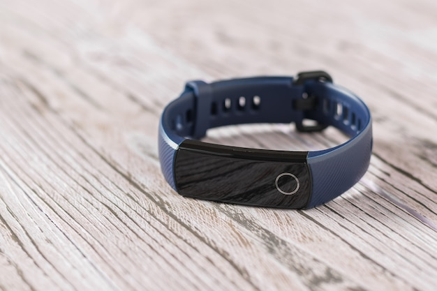 Modern smart bracelet with blue strap on wooden table. accessories to control sports. sports style.