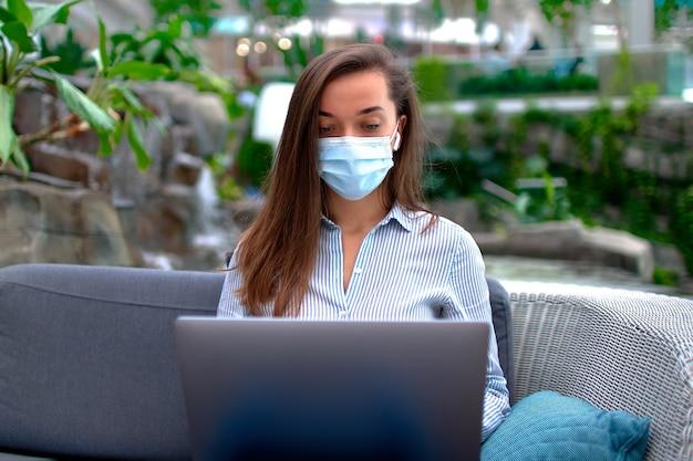 Современная умная женщина-фрилансер в медицинской маске удаленно работает онлайн за компьютером в общественном месте