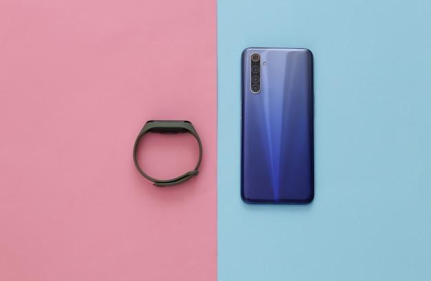 青ピンクのパステルカラーのモダンなスマートフォンとスマートブレスレット