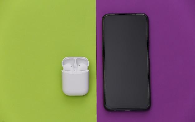 紫緑色の背景に充電ケース付きの最新のスマートフォンとワイヤレスイヤホン。