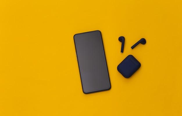 黄色の背景に充電ケースを備えた最新のスマートフォンとワイヤレスイヤホン。