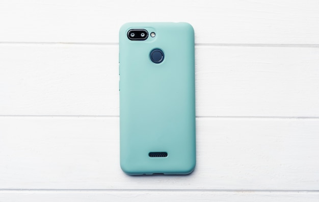 Modern smartphone in blues silicon case on the wooden floor centred with free for design space
