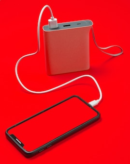 Modern smartphone charging with power bank isolated