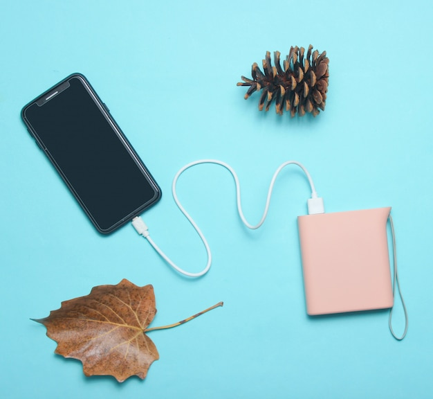 Modern smartphone charging with power bank, pin cone, autumn leaves on blue. top view