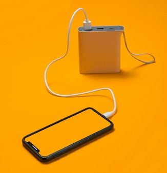 Modern smartphone charging with power bank on yellow.