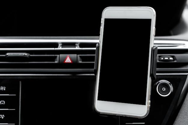 Современный гаджет для смартфона, закрепленный на держателе телефона на приборной панели автомобиля