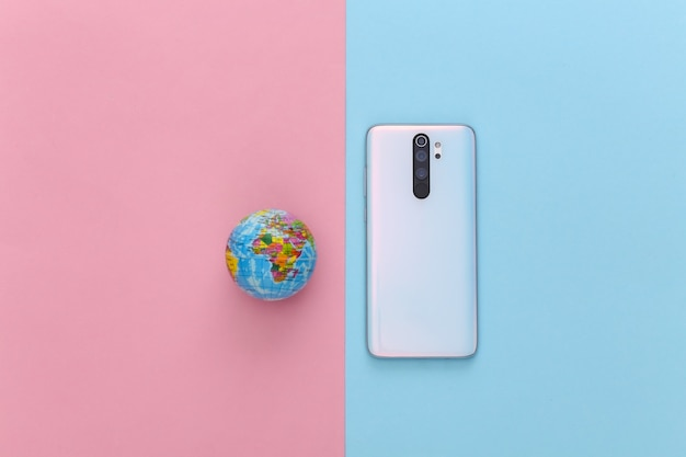 Modern smartphone and globe on a blue pink