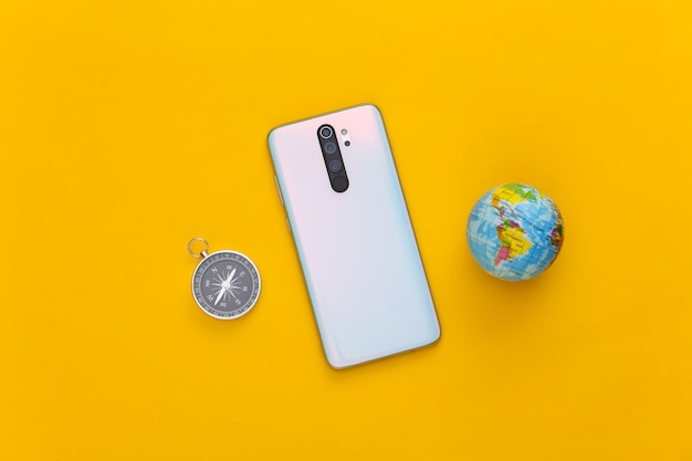 Modern smartphone and globe, compass on yellow. travel concept