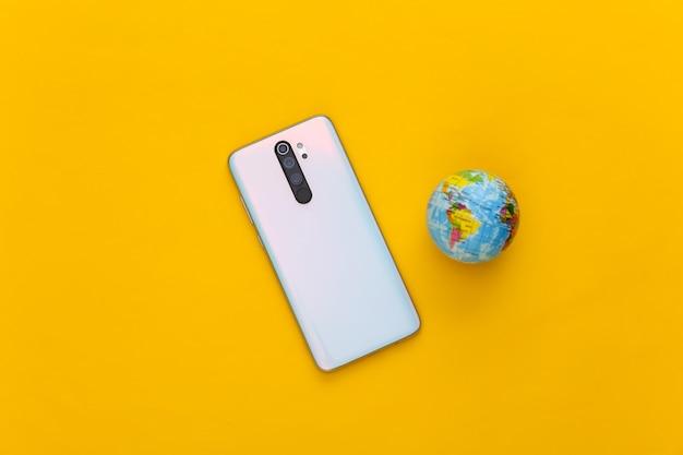 Modern smartphone and globe on yellow. global web